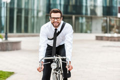 The best way to get to work. Happy young businessman smiling and looking at camera while riding on his bicycle Stock Image