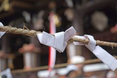 Best Wishes. Japanese Prayer Notes, omikuju charms, in temple of Kyoto, Japan.  Background is typical bell rope of temple Stock Photography