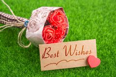 Best wishes. In card with heart and bouquet on grass royalty free stock image