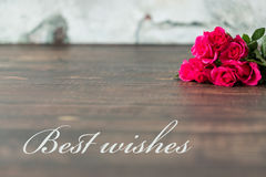 Best wishes for someone special. Shot of a table with a bunch of pink roses and a writing 'Best wishes Stock Images