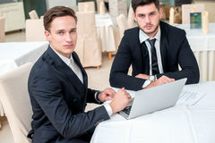 Best work. Two successful and confident businessman sitting at t. He table in a business office in full costume in the office and working at a laptop and looking Royalty Free Stock Image