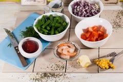 Bestandteile in den Schüsseln, Tomaten, Zwiebeln, Mais, Garnele, Lebensmittel, Rezept kochend Lizenzfreies Stockbild