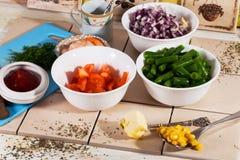 Bestandteile in den Schüsseln, Tomaten, Zwiebeln, Mais, Garnele, Lebensmittel, Rezept kochend Lizenzfreie Stockfotos