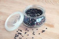 Bestandteile des heißen Gewürzs für Lebensmittel Stillleben mit den Samen des schwarzen Pfeffers innerhalb des runden Glasgefäßes Stockbilder