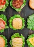 Bestandteile für Burger Neun Burger in den verschiedenen Stadien von Bereitschaft Ansicht von oben Schwarzer hölzerner Hintergrun Stockbilder