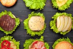Bestandteile für Burger Neun Burger in den verschiedenen Stadien von gelesen Lizenzfreie Stockbilder