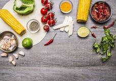 Bestandteile für Burritos mit Tomate, Pfeffer, würzigem Paprika, Mais, Käse und Knoblauch fassen Raum für Text auf grauem hölzern Stockfotos