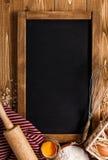 Bestandteile für das Backen auf hölzernem Hintergrund mit Kreidebrett für Stockfotos