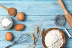 Bestandteile für das Backen, Milch, Eier, Weizenmehl und Küchengeschirr auf blauem hölzernem Hintergrund, Draufsicht stockbilder