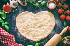 Bestandteile für das Kochen der Pizza oder der Teigwaren mit Teig in der Herzform stockfoto