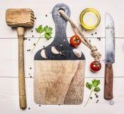 Bestandteile für das Kochen des Abendessens, des Knoblauchs, der Kirschtomaten, des Messers und des Hammers für Fleischfleisch, P Stockbild