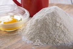 Bestandteile für das Kochen des Backens - Mehl, Ei, Plätzchenschneider auf w Stockfotos