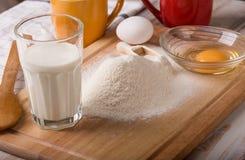 Bestandteile für das Kochen des Backens - Mehl, Ei, Plätzchenschneider auf w Lizenzfreie Stockfotografie