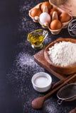 Bestandteile für das Kochen des Brotes auf einem dunklen Hintergrund, vertikal Lizenzfreie Stockfotografie