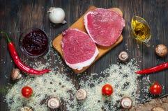 Bestandteile für das Kochen des gesunden Fleischabendessens Rohe ungekochte Rindfleischrippen-Augensteaks mit Pilzen, Reis, Kräut Lizenzfreies Stockbild