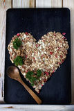 Bestandteile für das Kochen des gesunden Frühstücks in einer Form des Herzens Nüsse, Hafer blättert, Trockenfrüchte, Honig, Grano Lizenzfreies Stockfoto