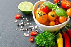 Bestandteile für das Kochen des Salats mit Kirschtomaten und chilis lizenzfreies stockbild