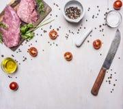 Bestandteile für das Kochen des Schweinefleischsteaks mit Gemüse und Gewürzen auf hölzernem rustikalem Draufsichtabschluß des Hin Stockfotografie
