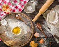 Bestandteile für das Kochen des Teigs oder des Brotes Defektes Ei auf ein Bündel weißes Roggenmehl Dunkler hölzerner Hintergrund Lizenzfreies Stockfoto