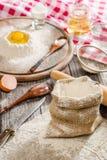 Bestandteile für das Kochen des Teigs oder des Brotes Defektes Ei auf ein Bündel weißes Roggenmehl Dunkler hölzerner Hintergrund Stockfotografie