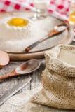 Bestandteile für das Kochen des Teigs oder des Brotes Defektes Ei auf ein Bündel weißes Roggenmehl Dunkler hölzerner Hintergrund Lizenzfreie Stockfotografie