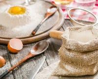 Bestandteile für das Kochen des Teigs oder des Brotes Defektes Ei auf ein Bündel weißes Roggenmehl Dunkler hölzerner Hintergrund Lizenzfreie Stockbilder