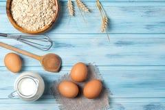 Bestandteile für das Kochen, Milch, Eier, Hafer und Küchengeschirr auf blauem hölzernem Hintergrund, Draufsicht lizenzfreie stockfotos
