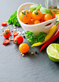 Bestandteile für das Kochen mit gelben Kirschtomaten, Kräuter, chil stockfotos