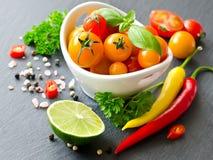 Bestandteile für das Kochen mit Kirschtomaten, Kräuter, chilis, Lim stockfotografie