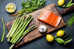 Bestandteile für das Kochen Rohes Lachsfilet, Spargel und Kräuter auf hölzernem Brett Lebensmittel, das Hintergrund mit Kopienrau stockfotografie