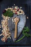 Bestandteile für das Kochen von gesunden Frühstück Nüssen, Hafer blättert, Trockenfrüchte, Honig, Granola ab Auf dunklem backgoun Stockfotos