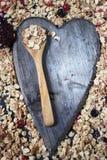Bestandteile für das Kochen von gesunden Frühstück Nüssen, Hafer blättert, Trockenfrüchte, Honig, Granola, hölzernes Herz ab Lizenzfreie Stockfotos