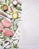 Bestandteile für das Kochen von Schweinefleisch mit Kräutern und Pfeffergrenze, Platz für Draufsicht des hölzernen rustikalen Hin Lizenzfreies Stockfoto