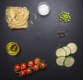 Bestandteile für das Kochen von vegetarischen Teigwaren mit Zucchini, Kirschtomaten, Erbsen und Pfeffer, legten rustikale Tafel,  Lizenzfreie Stockfotografie