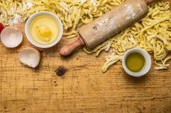 Bestandteile für das Kochen von vegetarischen Teigwarentomaten, Butter, Eier, Nudelholz auf hölzernem rustikalem Draufsichtabschl Lizenzfreie Stockbilder