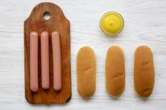 Bestandteile für die Herstellung von Hotdogen: Würste auf hölzernem Brett, Hot-Dog-Brötchen und Senf auf weißem hölzernem Hinterg lizenzfreie stockbilder