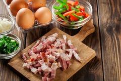 Bestandteile für die Zubereitung des Omeletts mit Speck und Gemüse Stockfoto