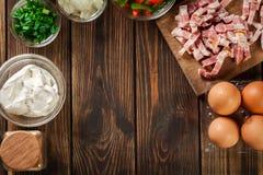 Bestandteile für die Zubereitung des Omeletts mit Speck und Gemüse Stockfotos