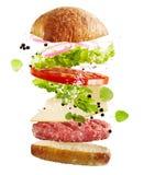 Bestandteile für einen Hamburger, der in einer Luft schwimmt Stockbild