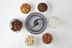 Bestandteile für Energiebisse: Nüsse, Daten, Kakaopulver und Kokosnussflocken mit Küchenmaschine auf weißer Tabelle lizenzfreies stockfoto