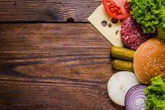 Bestandteile für Hamburger auf Holztisch, Grenzhintergrund Stockfoto