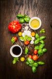 Bestandteile für Salat mit Mozzarella und Tomaten: Öl, Balsamico-Essig und frischer Basilikum auf dunklem rustikalem hölzernem Hi stockfotografie