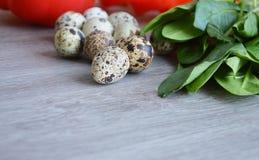 Bestandteile für Salat mit Wachteleiern und -spinat auf einem hölzernen Brett Lizenzfreies Stockbild