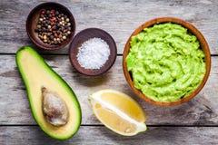 Bestandteile für selbst gemachtes Guacamolen: Avocado, Zitrone, Salz und Pfeffer Lizenzfreies Stockbild