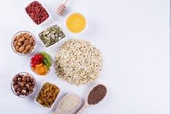 Bestandteile für selbst gemachtes Hafermehlgranola Haferflocken, -honig, -nüsse, -Trockenfrüchte und -samen Stockfoto