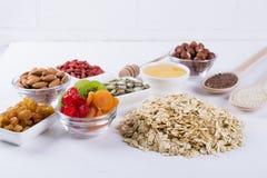 Bestandteile für selbst gemachtes Hafermehlgranola Haferflocken, -honig, -nüsse, -Trockenfrüchte und -samen Stockbilder