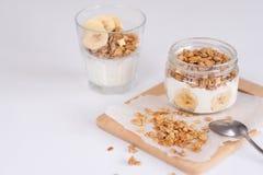 Bestandteile für selbst gemachtes Hafermehlgranola im Glasgefäß Haferflocken, -honig, -rosinen und -nüsse gesundes Frühstückskonz Stockbilder