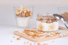 Bestandteile für selbst gemachtes Hafermehlgranola im Glasgefäß Haferflocken, -honig, -rosinen und -nüsse gesundes Frühstückskonz Stockbild