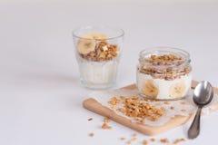 Bestandteile für selbst gemachtes Hafermehlgranola im Glasgefäß Haferflocken, -honig, -rosinen und -nüsse Gesundes Frühstückskonz Stockfoto