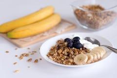 Bestandteile für selbst gemachtes Hafermehlgranola im Glasgefäß Haferflocken, -honig, -rosinen und -nüsse Gesundes Frühstückskonz Lizenzfreie Stockfotografie